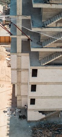 High angle view of a building under construction with unfinished concrete staircases and construction site safety net which can sustain heavy jerks.