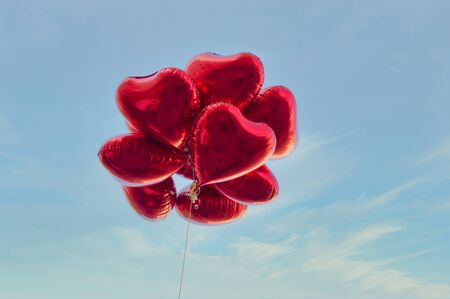 Group of heart shaped red air baloon on blue sky with clouds. Valentine's day and romance concept.