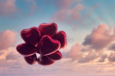 Group of heart shaped red air baloon on dramatic sky with pink clouds. Valentine's day and romance concept. Stok Fotoğraf