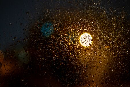 Raindrops on a window with the city lights at night, abstract blurred background with colored lights.