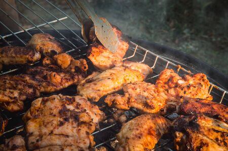 Flipping a barbecued chicken meat with tongs on a charcoal barbeque grill. Tasty snack party. Stok Fotoğraf - 150026555