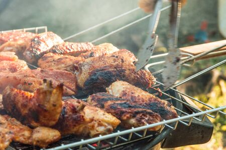 Flipping a barbecued chicken meat with tongs on a charcoal barbeque grill. Tasty snack party.