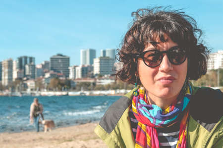 Outdoor portrait of pretty curly woman with colorful clothings and sunglasses, sitting on the beach with sea background. Urban lifestyle. Emotional expression.