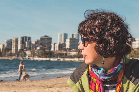 Profile of a brunette woman with curly hair, colorful clothings and sunglasses, sitting on sandy beach and looking away. Urban lifestyle. Emotional expression.