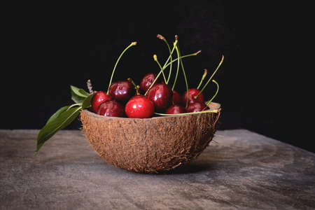 Fresh cherries in a coconut shell bowl on a wooden table on black background. Healthy eating.