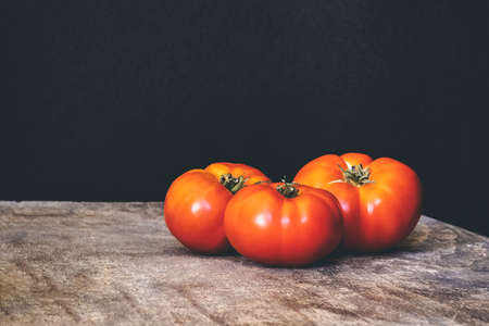 Three organic red tomatoes on a wooden table on a black background. Healthy eating. Stok Fotoğraf