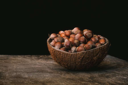 Pile of shelled hazelnuts in a coconut shell bowl on a wooden table on black background. Healthy eating.