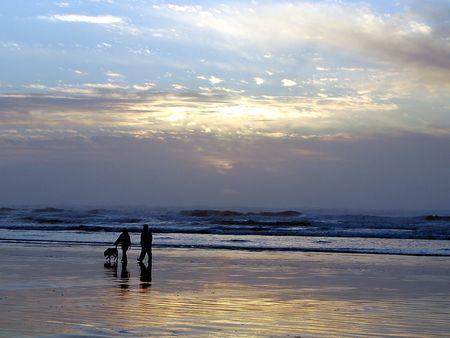 Couple walking dog on beach at sunset Stock Photo