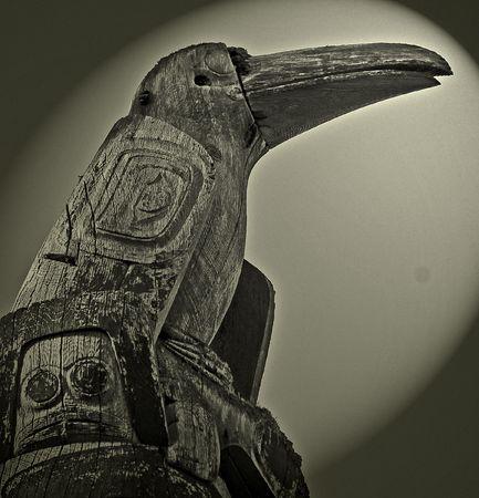 northwest indian art: Raven totem pole Stock Photo