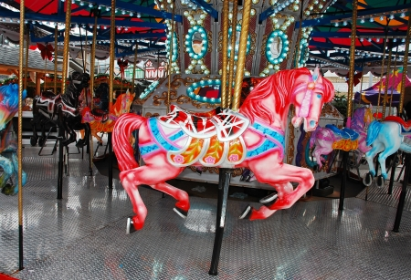 Pink carousel horse on colorful merry-go-round