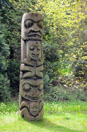 Weathered totem pole in pacific northwest forest