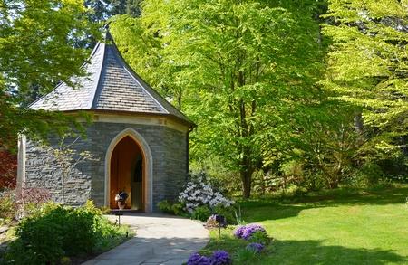 Brick gazebo in lush green garden setting photo