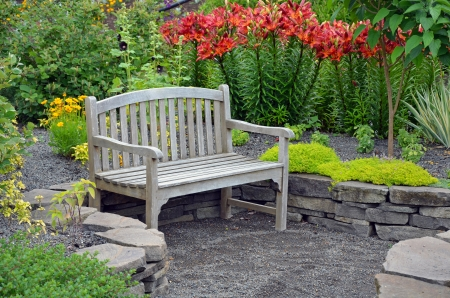 banc de parc: Banc en bois dans le jardin de fleurs de lys Banque d'images