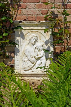 plaque: Mary and baby Jesus stone plaque on brick wall Stock Photo