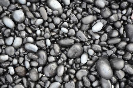Shiny black lava pebbles on oregon beach