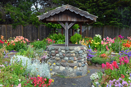 wishing: Old brick wishing well in colorful dahlia garden