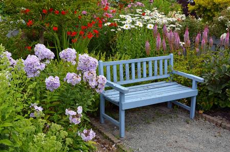 Oude blauwe houten tuinbank in kleurrijke zomer tuin