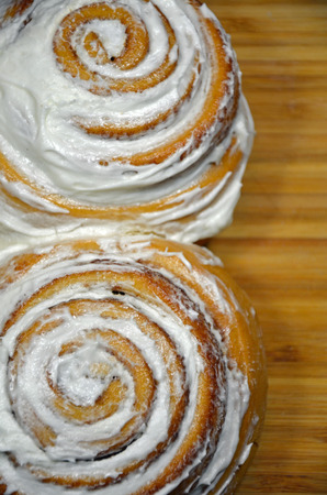 icing: Two cinnamon rolls with white icing