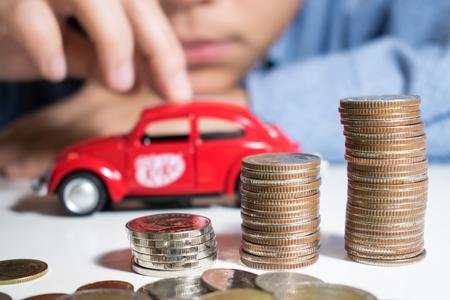 Azië, een man met een blauw shirt, verzamelt veel geld om rode auto's te kopen. Geld besparen concept.