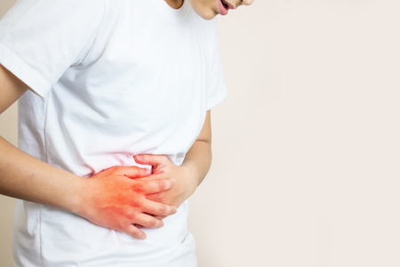 A woman wearing a white shirt feels a stomach ache on the right side. Stockfoto