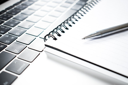 A close up photo of a pen placed on a notebook and computer.