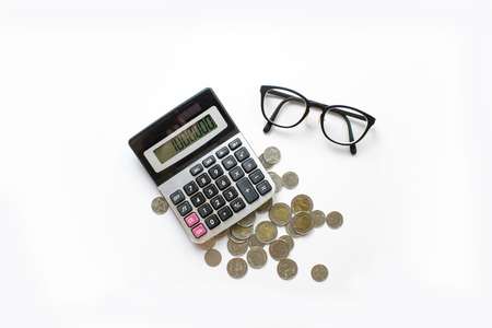 Business background. Financial calculations with calculator, coins and eye glasses on a white desk. 版權商用圖片 - 122657906
