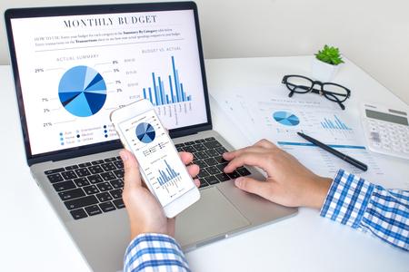 Los empresarios asiáticos utilizan equipos para los negocios. Sosteniendo un teléfono inteligente que funciona con computadoras portátiles y teléfonos móviles, que muestra estadísticas y aplicaciones de software.