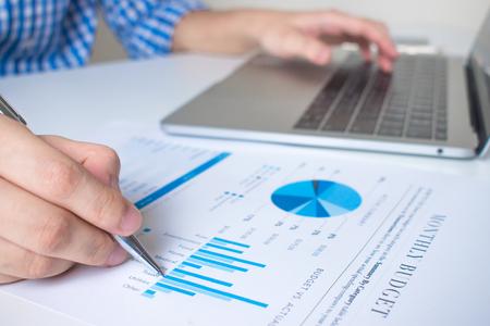 Imagen de primer plano de la mano de un trabajador de negocios que señala el gráfico con un bolígrafo sobre un escritorio blanco moderno. Foto de archivo