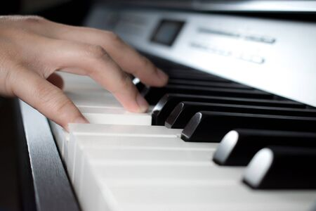 Musician playing the piano. Close up to the hand.