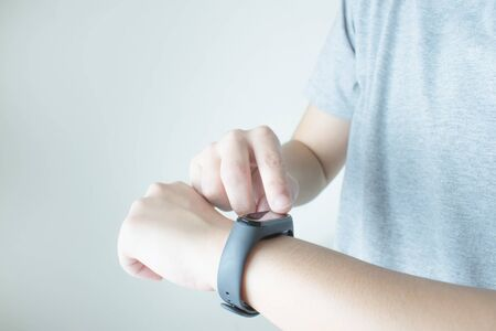 Women use touch hands on the black smartwatch screen in your hand. Imagens