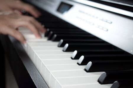 Blurred images of hands practicing piano in the music practice room. Imagens