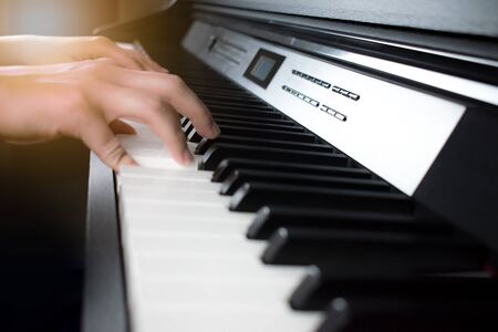 Young hands are playing the piano. Close-up.