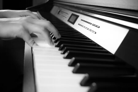 Young hands are playing the piano. Side view