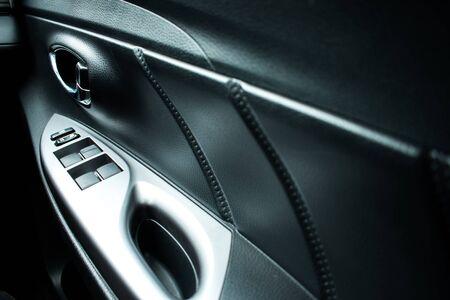 Car interior details of the door handle with control panel, window adjustment. Imagens