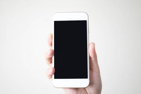 Hands holding a smart phone with a black screen at isolated background.