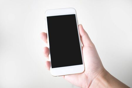 Young hands holding a smart phone on a white background.