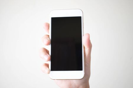 Young hands holding smart phones on a white background, top view