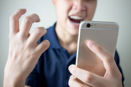 The young man felt angry from the smartphone with problems or errors. Imagens