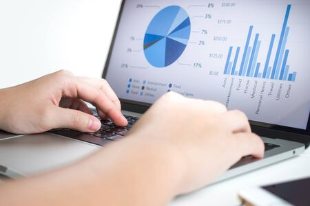 Businessmen use laptops to analyze statistics. Look at the presentation screen with graphs and financial report diagrams. Imagens