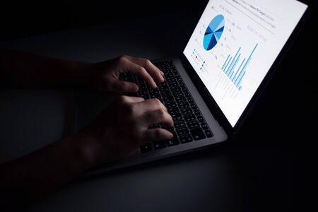 Hands are using laptop financial graph displays in dark rooms. Imagens