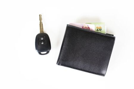 Leather purse with bank notes with car keys and isolated on a white background.