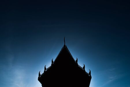 Silhouettes of Thai temples in the blue sky in the morning.