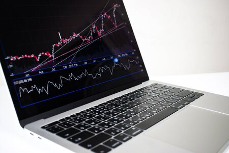 Close-up, Laptop computer image showing financial graph on screen with isolated on white background. Imagens