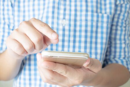 Asian people wear blue plaid shirts using smartphones, Close up.