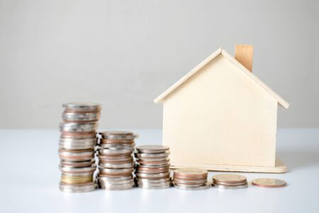 House models and coins on the table, saving money to buy a house in the concept of finance and banking.