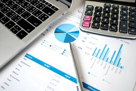 Financial graph with laptop and calculator on the desk Imagens
