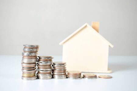 Coin stack and house plans. Property investment and house mortgage financial concept. Stockfoto - 128603517