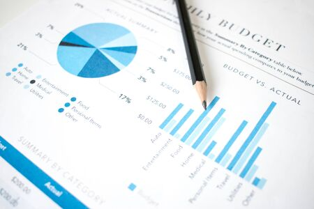 The pencil is placed on the financial graph of the businessman. Imagens
