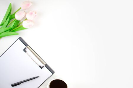 Top view image on a white table with tulips, clipboard, pens and coffee on a white background.