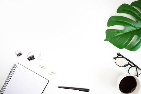Top view image on a white table workspace with laptop, palm leaf, notebook and accessories. Flat lay, top view copy space.